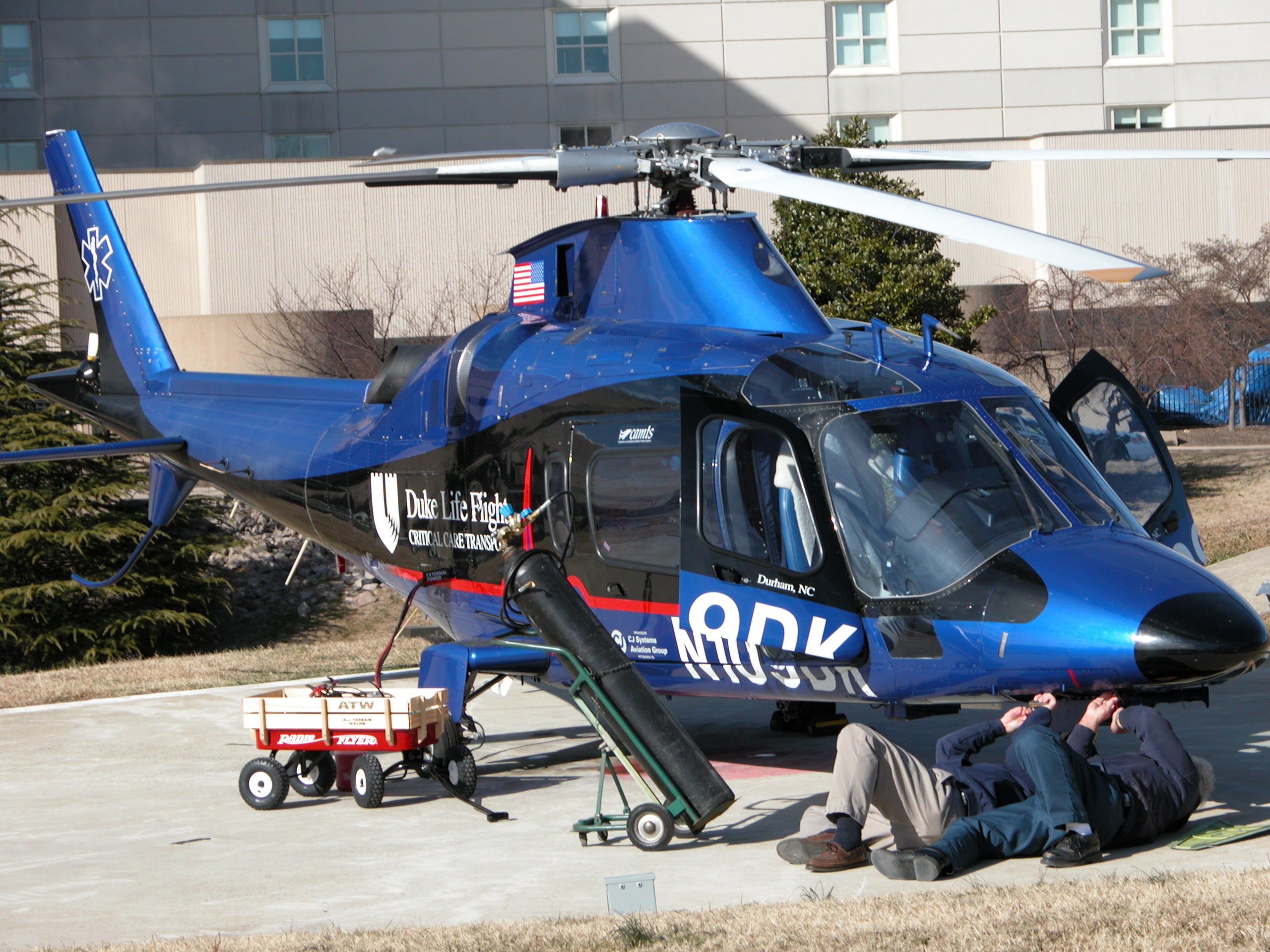 Two men performing helicopter repairs
