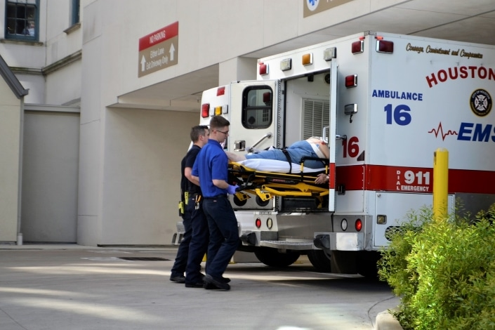 First responders lifting a stretcher into an ambulance